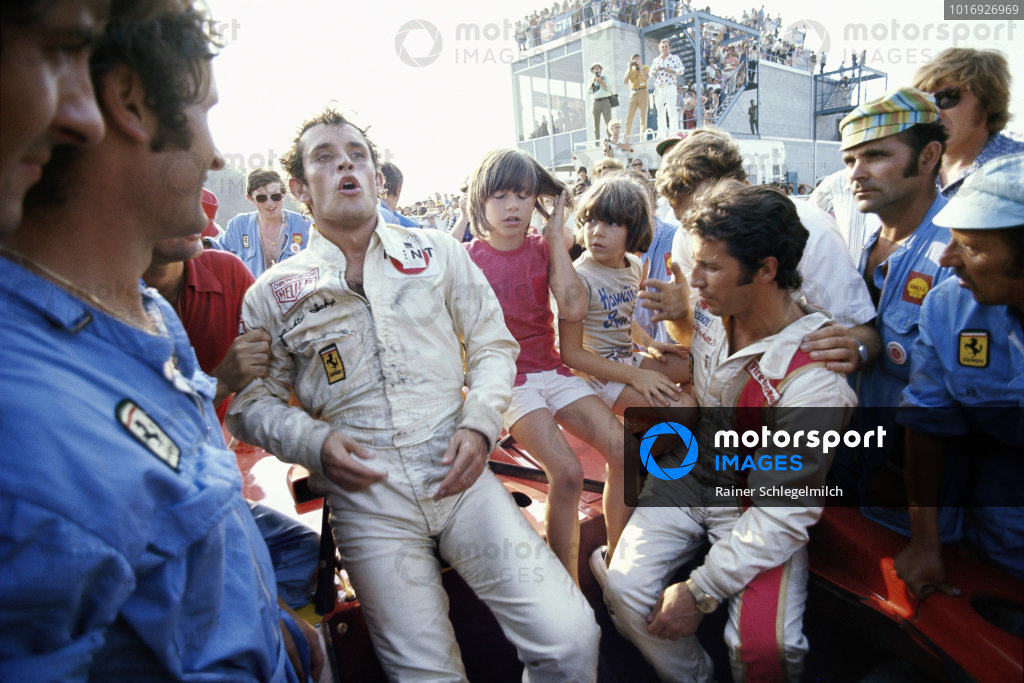 Jacky Ickx and Mario Andretti celebrate victory in their Ferrari 312PB surrounded by their mechanics and Mario's son Michael.