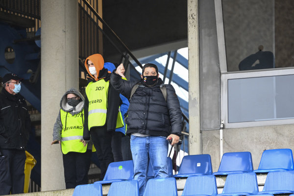 A fan in a grandstand gives the weather a thumbs down