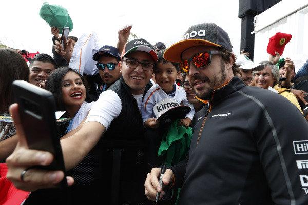 Fernando Alonso, McLaren, has his photo taken with fans