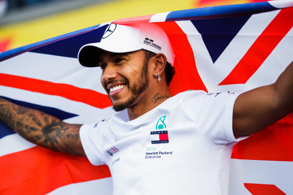 Lewis Hamilton, Mercedes AMG F1, with a Union flag over his shoulders, celebrates having secured his 5th world drivers championship crown with the Mercedes team