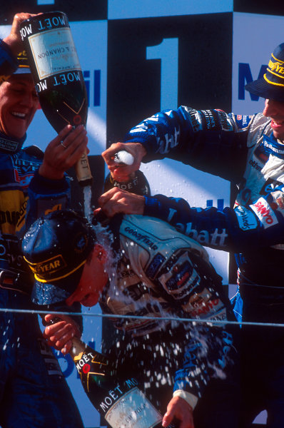 Estoril, Portugal.22-24 September 1995.Michael Schumacher (Benetton Renault) 2nd position and Damon Hill (Williams Renault) 3rd position give David Coulthard (Williams Renault) 1st position a champagne shower, for his maiden Grand Prix win on the podium.Ref-95 POR 04.World Copyright - LAT Photographic