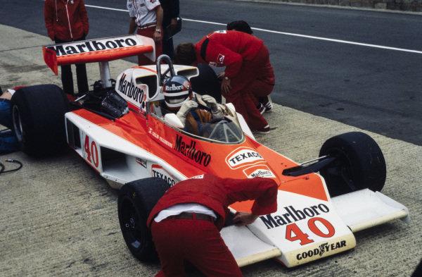 Mechanics work on Gilles Villeneuve's McLaren M23 Ford while he sits in the cockpit.