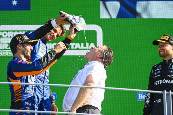 Daniel Ricciardo, McLaren, 1st position, and Lando Norris, McLaren, 2nd position, assist Zak Brown, CEO, McLaren Racing, in performing a shoey on the podium