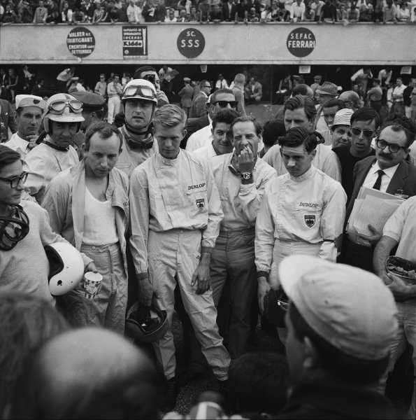 Monza, Italy. 14th - 16th September 1962. L to R: Masten Gregory, Roy Salvadori, John Surtees, Carel De Beaufort, Tony Maggs, Innes Ireland, Jim Clark and Graham Hill all listen in to the drivers briefing before the race, portrait. World Copyright: LAT Photographic. Ref: 10305.