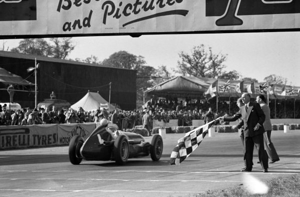 Reg Parnell, Alfa Romeo 158, takes the chequered flag for the final podium position.