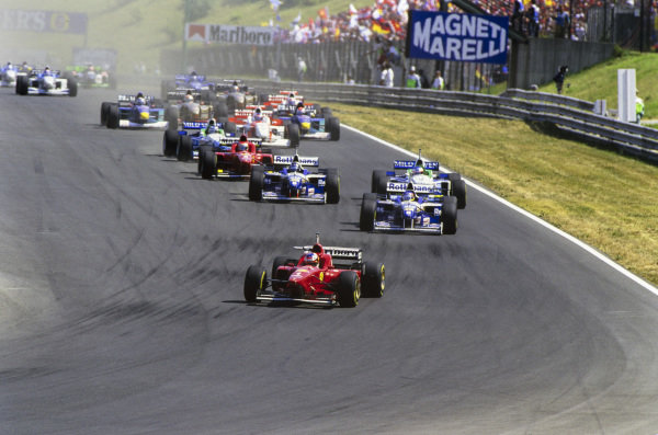 Michael Schumacher, Ferrari F310, leads Jacques Villeneuve, Williams FW18 Renault, Jean Alesi, Benetton B196 Renault, Damon Hill, Williams FW18 Renault, Gerhard Berger, Benetton B196 Renault, and the rest of the field at the start of the race.