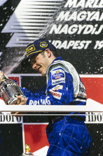 Jacques Villeneuve, 1st position, celebrates with champagne on the podium.