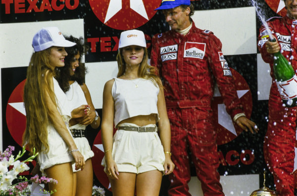 Glamour girls are admired on the podium by Niki Lauda, 2nd position. Behind, Alain Prost, 1st position, sprays champagne.