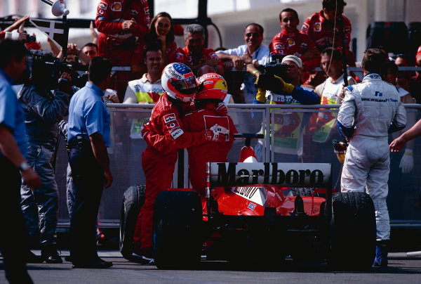 2002 Hungarian Grand Prix.Hungaroring, Budapest, Hungary. 16-18 August 2002.Rubens Barrichello is congratulated by team mate Michael Schumacher (both Ferrari) in parc ferme. Ralf Schumacher (Williams BMW) stands nearby. They finished in 1st, 2nd and 3rd positions respectively. Ref-02 HUN 33.World Copyright - Tee/LAT Photographic
