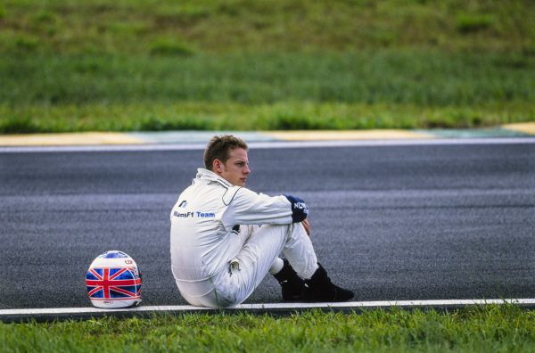 Jenson Button sits by the side of the circuit after retiring from a session.