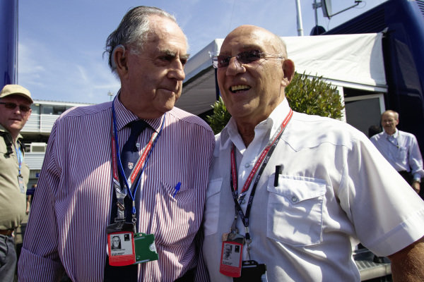F1 World Champion Sir Jack Brabham and racing legend Sir Stirling Moss in the paddock.