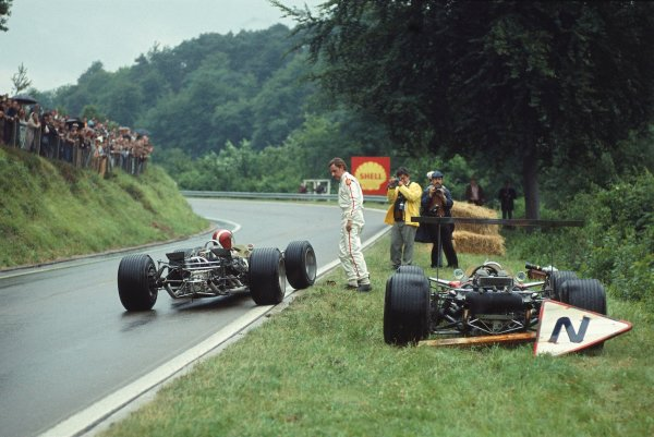 1968 French Grand Prix.Rouen-les-Essarts, France.5-7 July 1968.Graham Hill (Lotus 49 Ford) who had retired, gives his teammate Jo Siffert (Lotus 49 Ford) his visor on the trackside.Ref-68 FRA 12.World Copyright - LAT Photographic