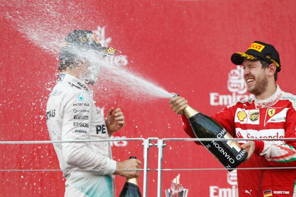 Baku City Circuit, Baku, Azerbaijan. Sunday 19 June 2016. Sebastian Vettel, Ferrari, sprays champagne at race winner Nico Rosberg, Mercedes AMG.  World Copyright: Glenn Dunbar/LAT Photographic ref: Digital Image _V2I3661