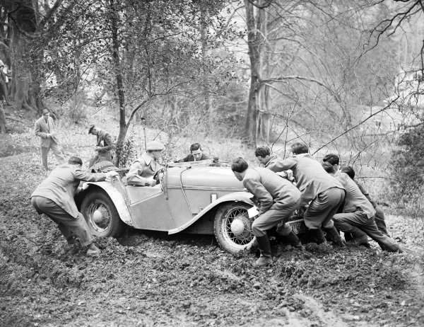 Spectators try to move a car stuck in mud.