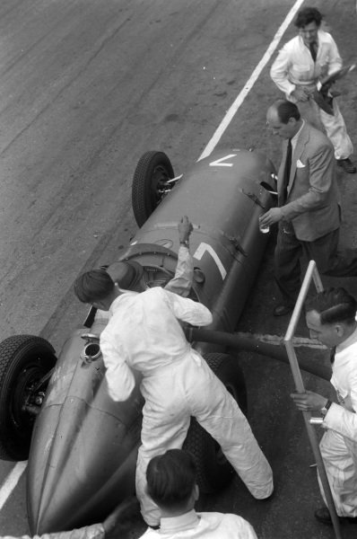 Peter Walker, BRM P15, reaches out for a drink as a mechanic prepares to refuel his car during a pitstop.
