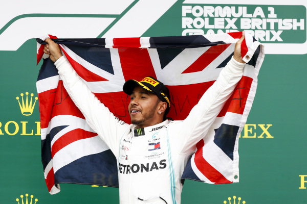 Race winner Lewis Hamilton, Mercedes AMG F1 celebrates on the podium with a flag