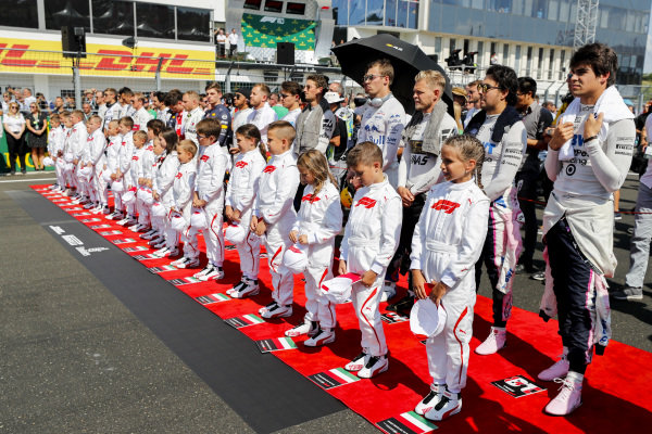 The Grid Kids are joined by the drivers for the national anthem prior to the start