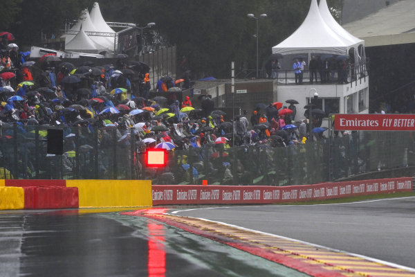 Puddles forming on the circuit and fans under umbrellas