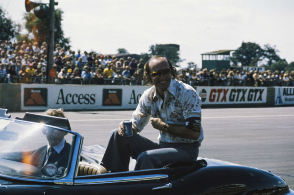 Mike Hailwood enjoys a beverage in the parade car.
