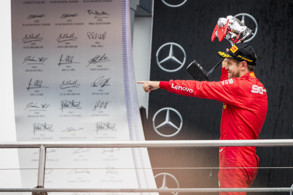 Sebastian Vettel, Ferrari celebrate on the podium with the trophy