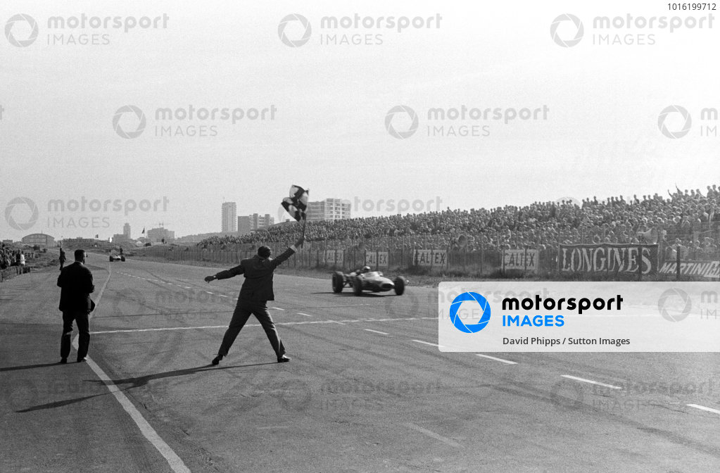 Race winner Jack Brabham (AUS) Brabham BT19 takes the chequered flag to score his hat-trick of consecutive victories. Dutch Grand Prix, Zandvoort, 24 July 1966.