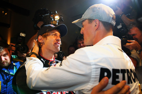 Michael Schumacher (GER) Mercedes GP congratulates 2010 World Champion Sebastian Vettel (GER) Red Bull Racing. Formula One World Championship, Rd 19, Abu Dhabi Grand Prix, Race, Yas Marina Circuit, Abu Dhabi, UAE, Sunday 14 November 2010.  BEST IMAGE