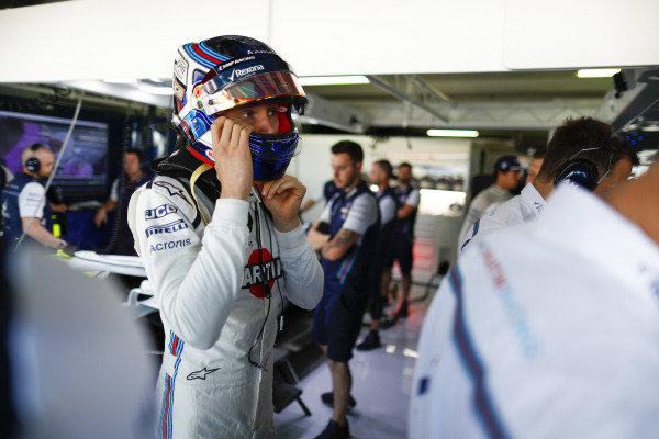 Sergey Sirotkin, Williams Racing, adjusts his helmet in the team's garage.
