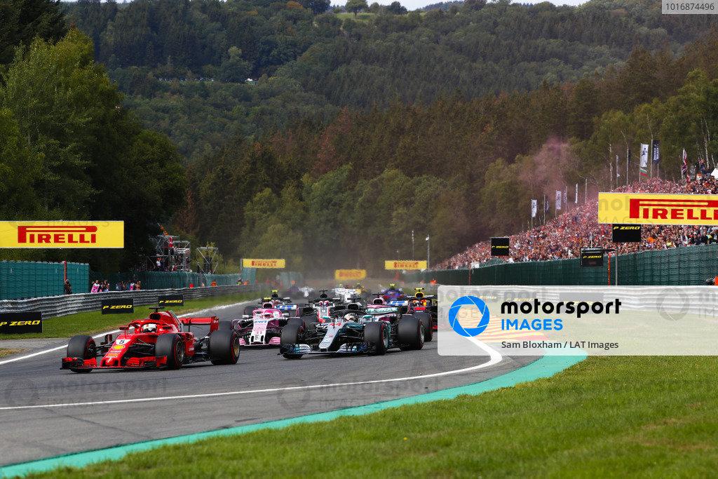 Sebastian Vettel, Ferrari SF71H, leads Lewis Hamilton, Mercedes AMG F1 W09, Esteban Ocon, Racing Point Force India VJM11, and Sergio Perez, Racing Point Force India VJM11, on the opening lap.