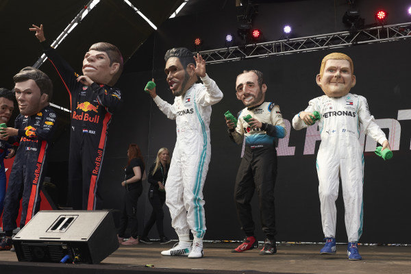 Caricatures of Pierre Gasly, Red Bull Racing, Max Verstappen, Red Bull Racing, Lewis Hamilton, Mercedes AMG F1, Robert Kubica, Williams Racing, and Valtteri Bottas, Mercedes AMG F1, on stage