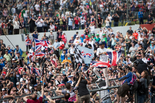 Silverstone, Northamptonshire, UK Sunday 10 July 2016. Lewis Hamilton, Mercedes AMG, 1st Position, celebrates victory at his home race with the fans. World Copyright: Ferraro/LAT Photographic ref: Digital Image _FER9066