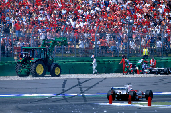 2004 German Grand PrixHockenheim, Germany. 23rd - 25th July.Kimi Raikkonen, McLaren Mercedes MP4/19 walks away from his car after crashing as a result of a rear wing failiure. Action. World Copyright:Charles Coates/LAT Photographic Ref:35mm Image:A08