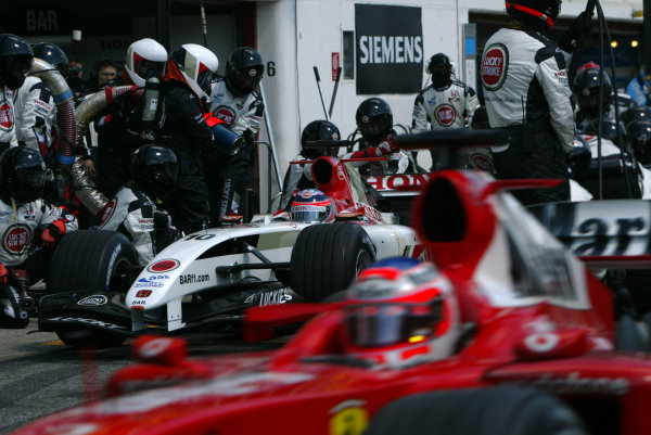 2004 San Marino Grand Prix-Sunday Race,Imola, Italy. 25 April 2004.Rubens barrichello passes as Takuma Sato undertakes a pitstop.World Copyright: LAT Photographic.Ref: Digital Image only.