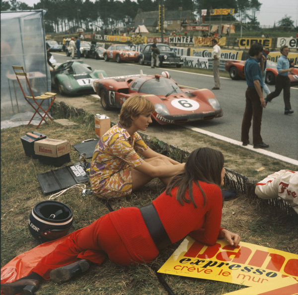 Two women sit beside the track during filming of the Steve McQueen movie Le Mans. A Ferrari 512S, Lola T70., Chevron, Porsche 911 and Porsche 914 are visible. The helmet of Jacky Ickx can be seen in the foreground