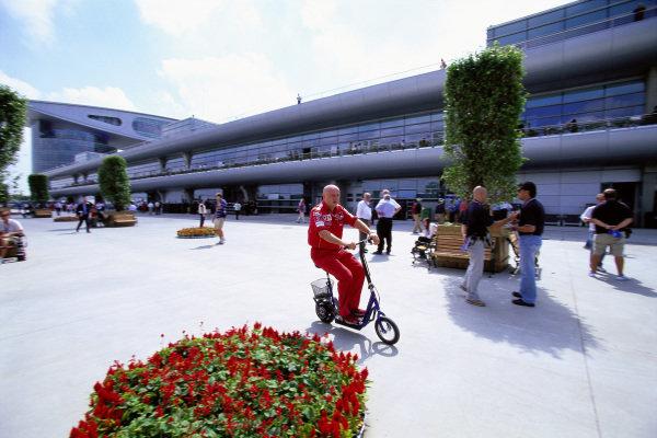 A Ferrari team member scoots through the paddock.