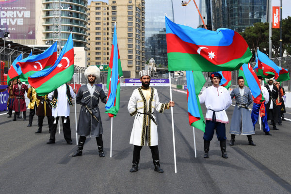 Flag holders in national costume on the grid