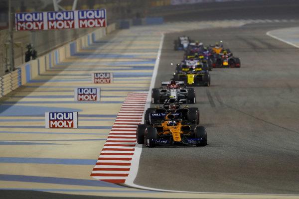 Carlos Sainz Jr., McLaren MCL34, leads Kevin Magnussen, Haas VF-19, and Kimi Raikkonen, Alfa Romeo Racing C38