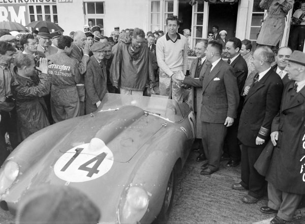 Phil Hill and Olivier Gendebien stand in their Ferrari 250 TR58 as they are congratulated on their victory.