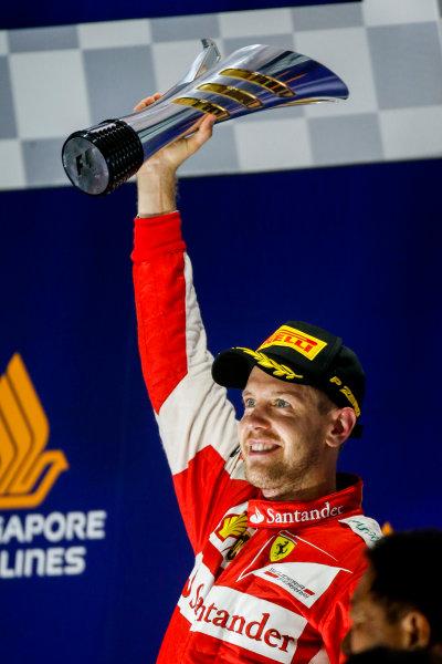 Marina Bay Circuit, Singapore. Sunday 20 September 2015. Sebastian Vettel, Ferrari, 1st Position, raises his trophy on the podium. World Copyright: Glenn Dunbar/LAT Photographic. ref: Digital Image _89P6019