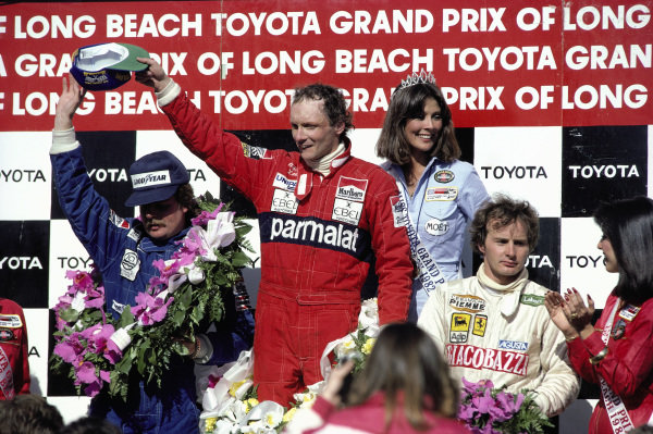 Niki Lauda, 1st position, celebrates on the podium, with Keke Rosberg, 2nd position, and Gilles Villeneuve, 3rd position.