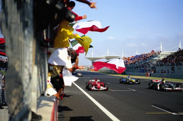 Ferrari mechanics wave flags from the pit wall as Rubens Barrichello, Ferrari F2004 claims victory.