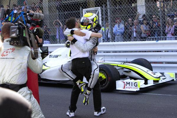 Race winner Jenson Button jumps on Brawn GP CEO Nick Fry in parc ferme.