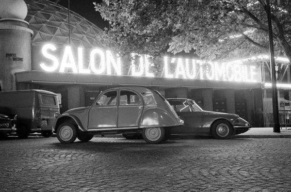 Citroen 2CV in front of the Parc des Expositions with illuminated Salon de l'Automobile sign.