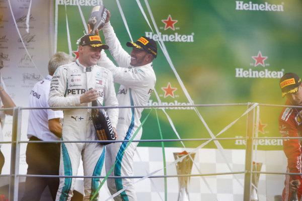 Lewis Hamilton, Mercedes AMG F1, 1st position, pours Champagne over Valtteri Bottas, Mercedes AMG F1, 3rd position, on the podium.