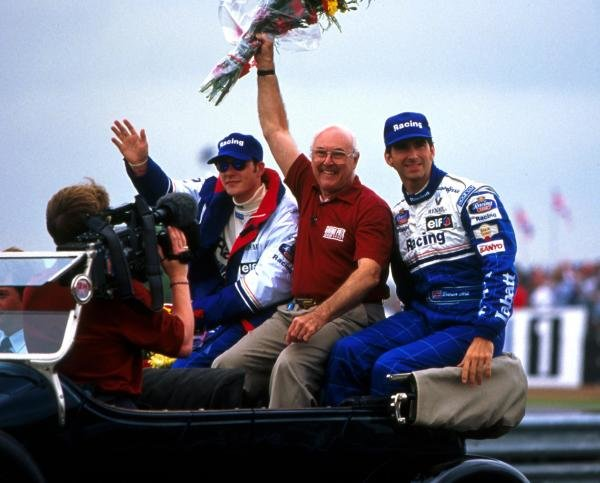 BBC Grand Prix commentator Murray Walker (GBR) waves to the crowds. Beside him are Rothmans Williams drivers Damon Hill (GBR), right, and Jacques Villeneuve (CDN), left.