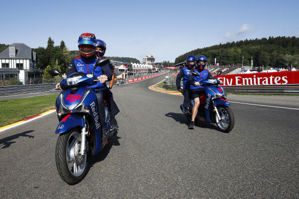Brendon Hartley rides a moped with Toro Rosso colleagues.