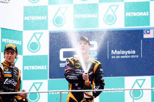 Sepang, Kuala Lumpur, Malaysia. 25th March 2012. Sunday Race.James Calado (GBR, Lotus GP) celebrates his victory on the podium with Esteban Gutierrez (MEX, Lotus GP).World Copyright: Alastair Staley/GP2 Series Media Service.Ref: Digital Image AS5D7697.jpg