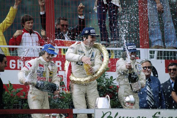 Alan Jones, 1st position, celebrates on the podium with Gilles Villeneuve, 2nd position, and Jacques Laffite, 3rd position.
