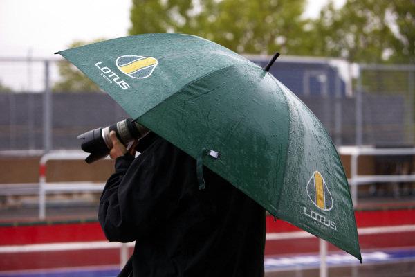 Circuit Gilles Villeneuve, Montreal, Canada10th June 2010A photographer keeps out of the rain, under a Lotus Racing umbrella. Atmosphere. World Copyright: Steve Etherington/LAT Photographicref: Digital Image SNE24236