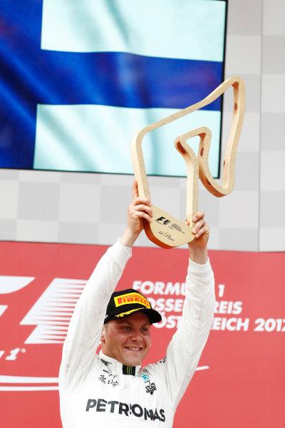 Red Bull Ring, Spielberg, Austria. Sunday 09 July 2017. Valtteri Bottas, Mercedes AMG, raises his winner's trophy on the podium. World Copyright: Glenn Dunbar/LAT Images ref: Digital Image _31I7805