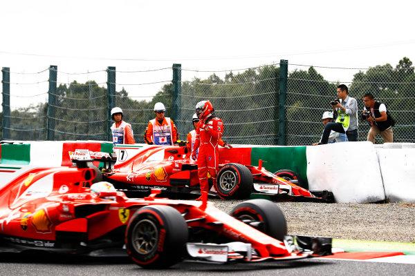 Suzuka Circuit, Japan. Saturday 07 October 2017. Sebastian Vettel, Ferrari SF70H, passes Kimi Raikkonen, Ferrari SF70H, as he climbs from his car after crashing. World Copyright: Steven Tee/LAT Images  ref: Digital Image _O3I7189